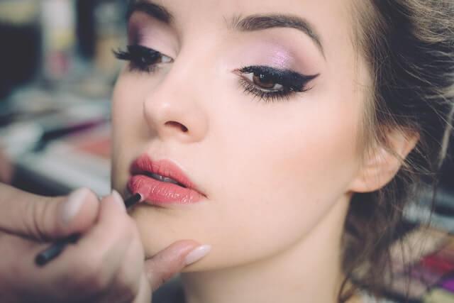 Jeune femme se faisant maquillage la lèvre inférieure