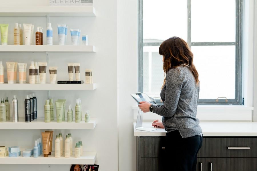 coiffeuse dans un salon qui cherche un produit capillaire