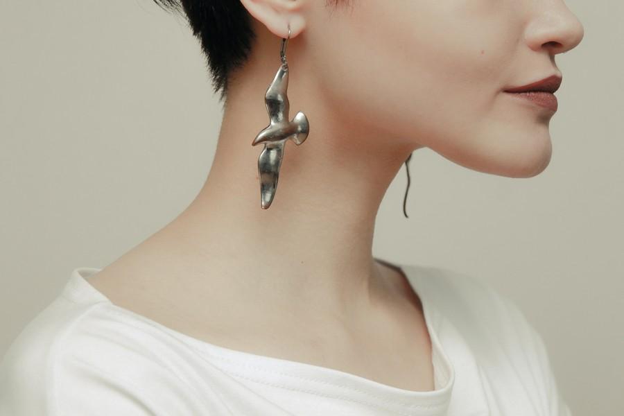 femme de profil qui porte des boucles d'oreilles pendentifs