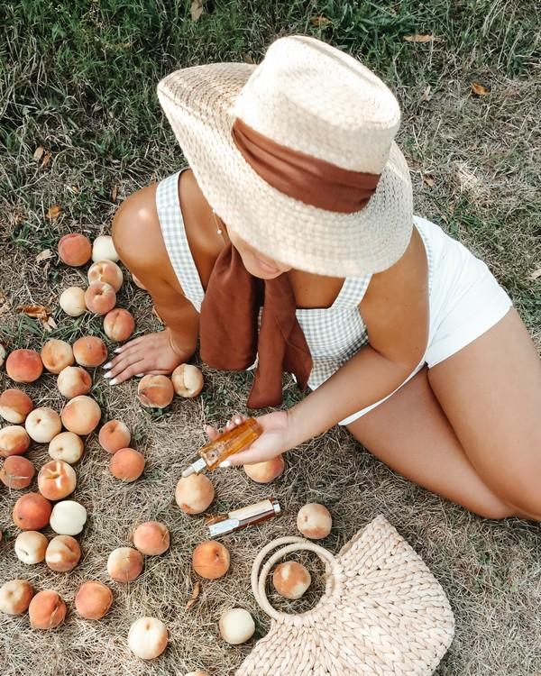 femme en maillot de bain assise au milieu d'abricots qui porte un chapeau de soleil et tient une crème solaire