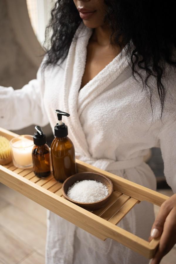 femme en peignoir prête à prendre son bain et faire des soins cheveux avec de l'huile d'argan
