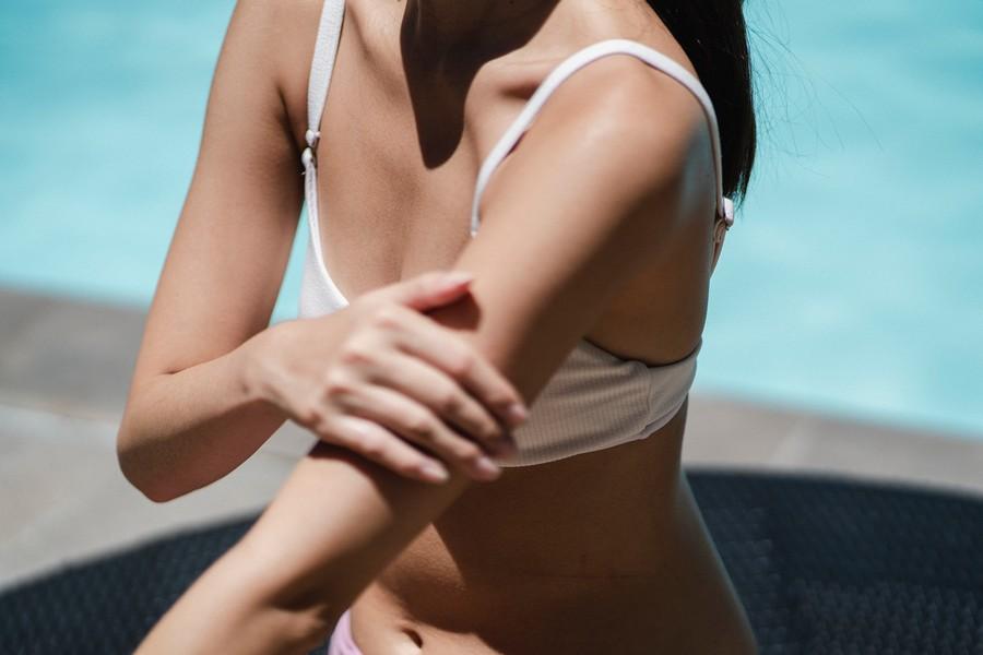 femme qui s'applique de la crème solaire sur les bras
