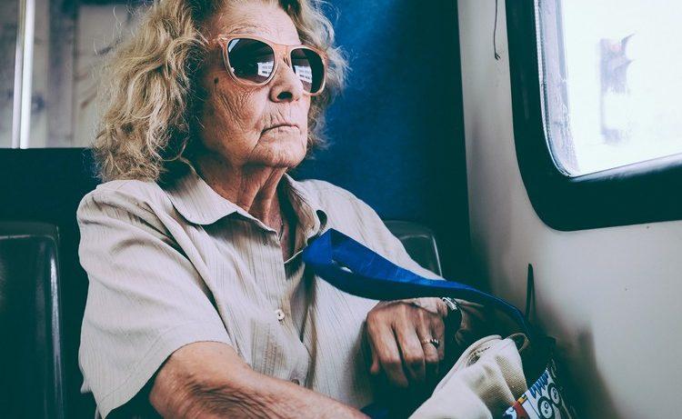 veille dame dans le train qui cherche quelque chose dans son sac