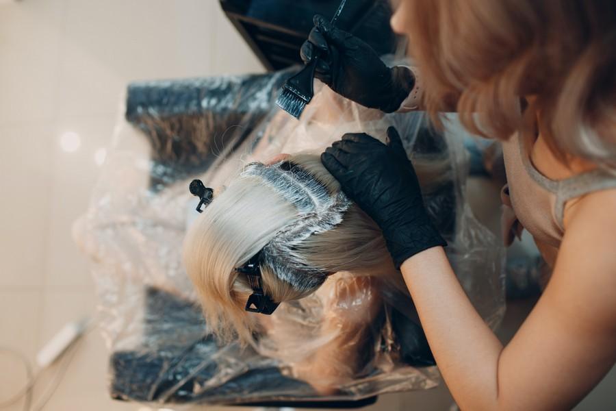 coiffeuse en train de colorer les cheveux d'une cliente