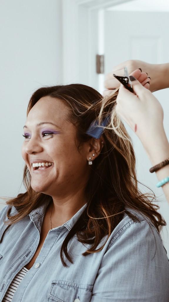 femme souriante qui se fait couper les cheveux chez le coiffeur