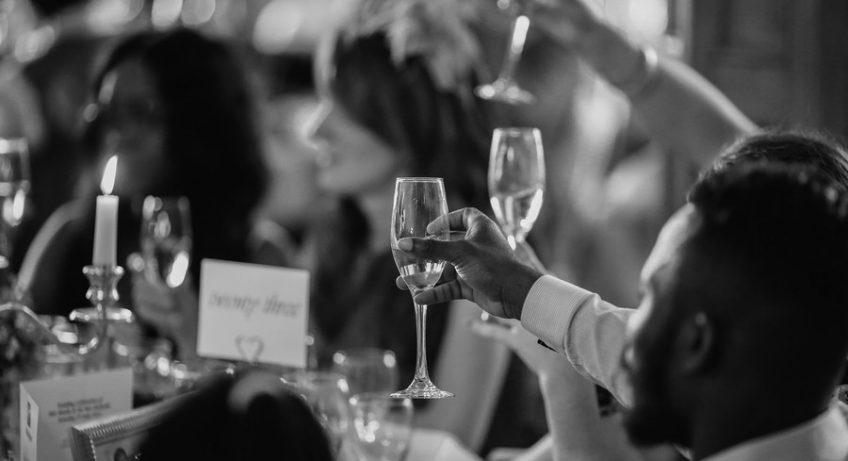 invités à un mariage qui lèvent leurs verres pour le discours
