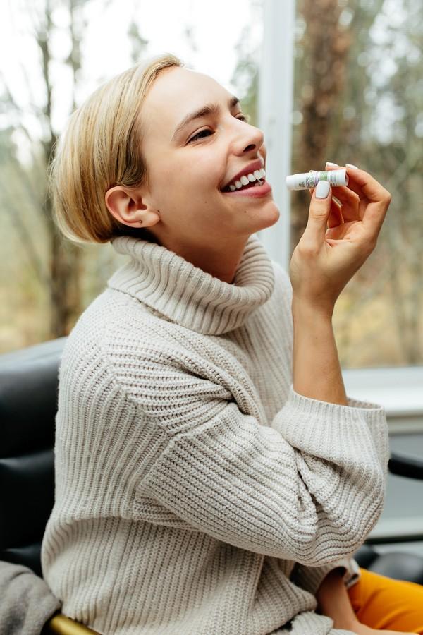 jeune femme qui applique du baume à lèvres