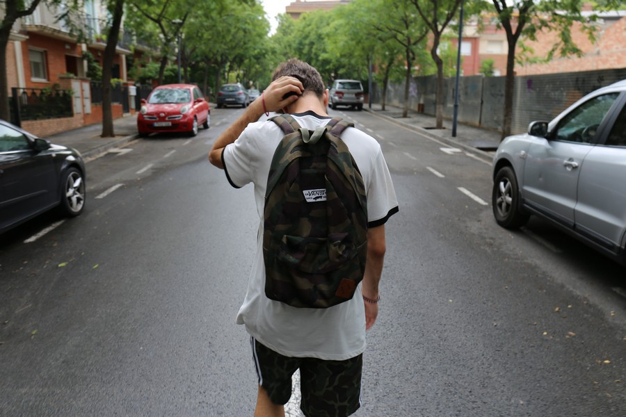 jeune garçon dans la rue qui porte un sac à dos