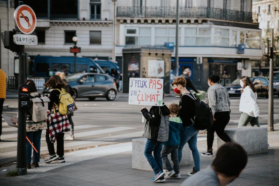 manifestation avec un enfant qui porte une pancarte avec l'inscription je peux pas j'ai climat