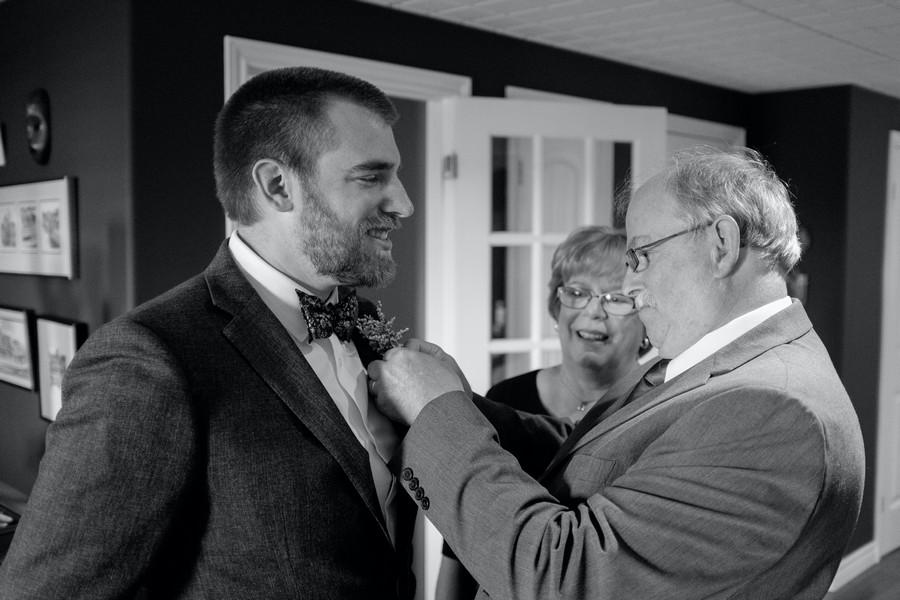parents qui ajustent le nœud papillon de leur fils qui va se marier