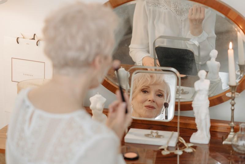 femme d'un certain âge qui se maquille devant sa coiffeuse