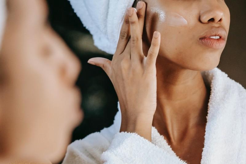 femme en peignoir qui applique de la crème sur son visage