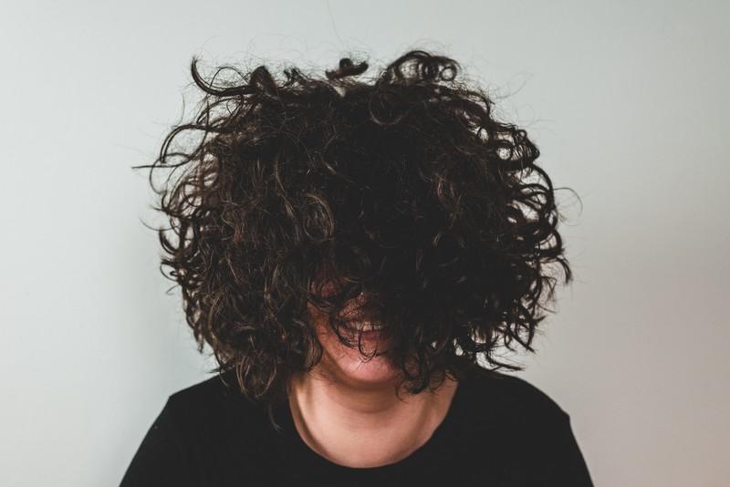 femme mal coiffée aux cheveux bouclés et avec des frisottis