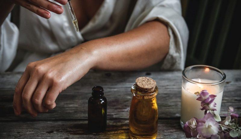 femme qui s'applique de l'huile essentielle sur l'avant bras