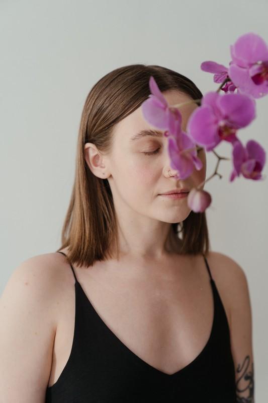 femme qui sent une orchidée