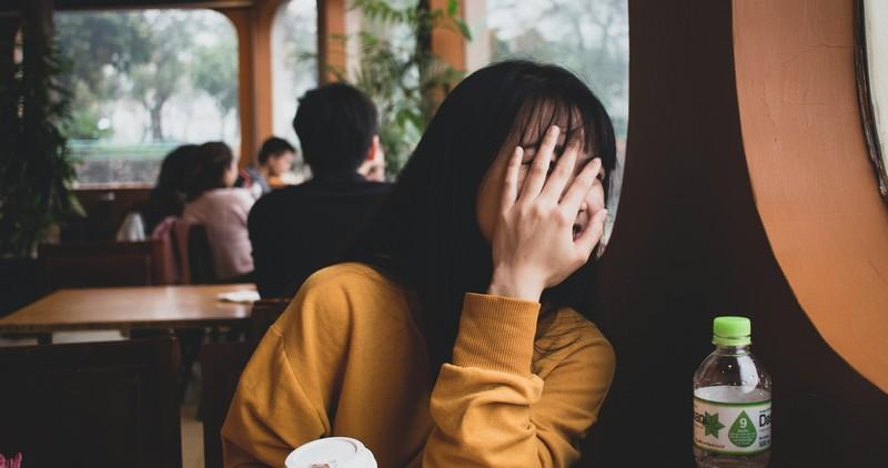 femme timide qui se cache derrière sa main