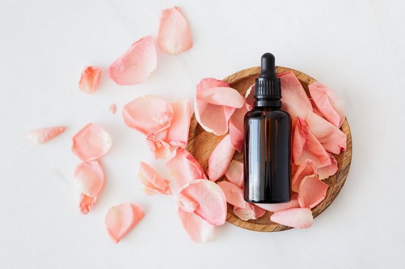 flacon d'eau florale posé sur un tas de pétales de rose