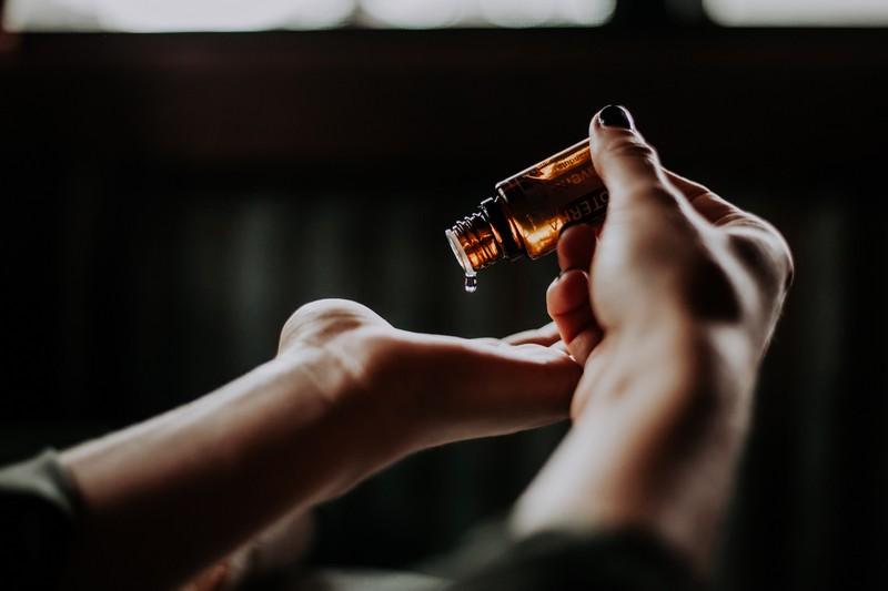 main d'une personne qui s'applique de l'huile essentielle dans la paume