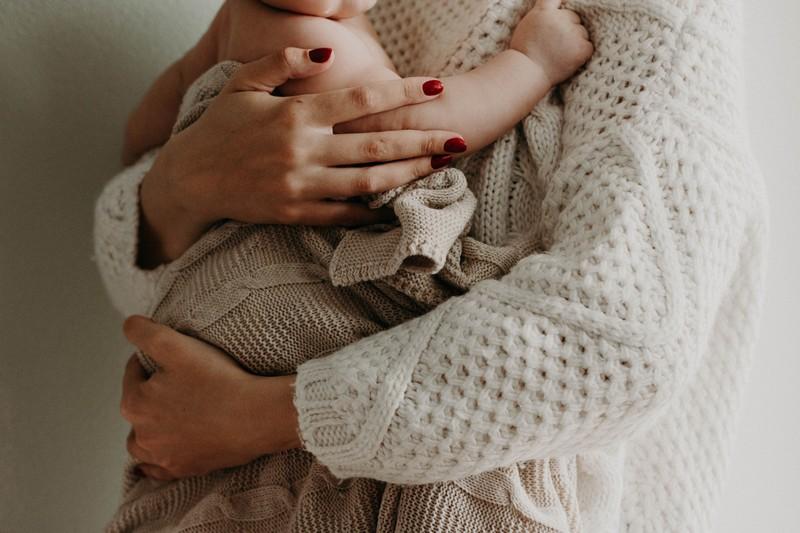 maman qui porte son bébé en peau à peau avec une couverture