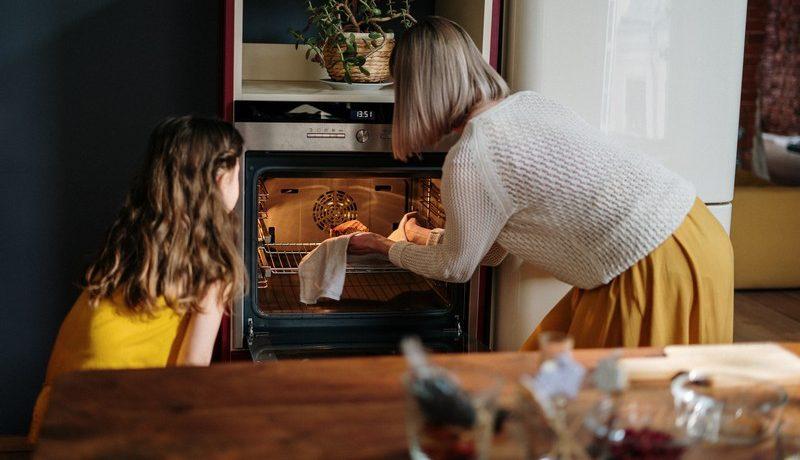 maman et son enfant qui sort un gâteau du four