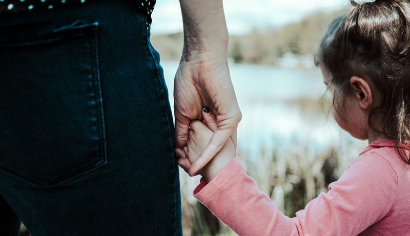 petite fille qui tient la main de sa maman