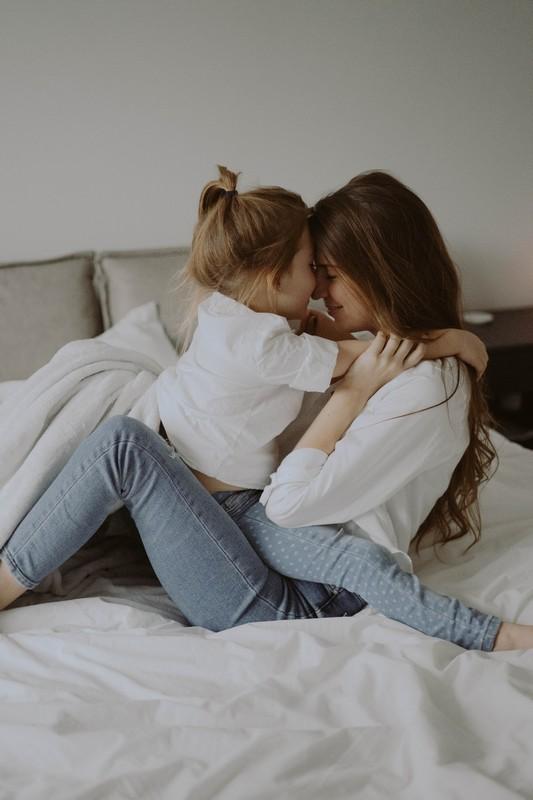 une maman et sa fille qui font un câlin sur un lit